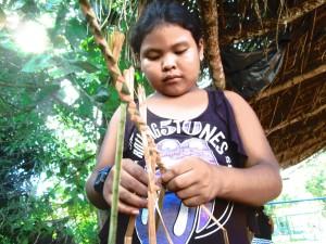 Crianças aprendem a fazer tranças de taboa, o primeiro passo para a fabricação de cestas